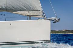 Sailboat bow with hoisted headsail and copy space on the boat hull. Stock Photography