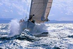 Sailboat breaking through the splashing wave royalty free stock image