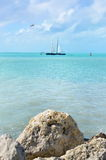 Sailboat in bright blue water Stock Images