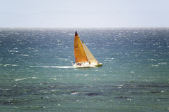 A sailboat with a bright orange sail gliding Stock Photography