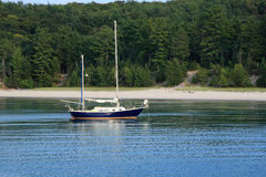 Sailboat on calm lake. With beach behind it Stock Photos