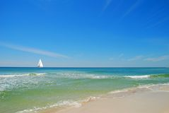 Sailboat on Calm Sea. Beautiful beach and breaking surf with sailboat on horizon Royalty Free Stock Images