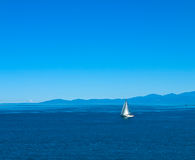 Sailboat in calm waters. Sailboat blissfully cruising in calm coastal waters with mountains in background Royalty Free Stock Photography