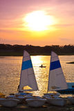 Sailboat and Canoeing in a beautiful lake at Sunset Stock Photos