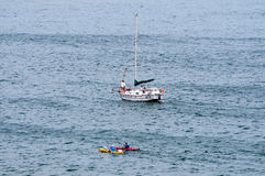 Sailboat and canoes in the sea near Gordons Bay Royalty Free Stock Photography
