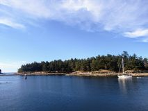 A sailboat carefully navigating a passage with reefs in the Gulf Islands, British Columbia, Canada. royalty free stock photos