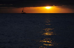 Sailboat Challenges Dramatic Tropical Sunset, Hawaii. A stunning amber sunset is the background for the silhouette of a sailboat off the coast of Maui, Hawaii as Royalty Free Stock Image