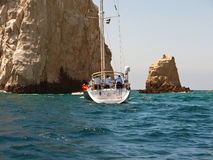 Sailboat close to the rocks. With tourist admiring the scenery Stock Photography