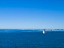 Sailboat in coastal waters royalty free stock images