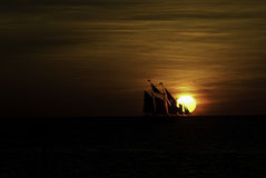Sailboat crossing the setting sun Royalty Free Stock Images