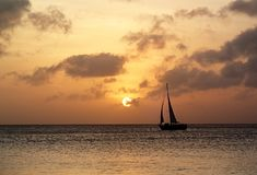 Sailboat Crossing at Sunset. Sailboat crossing the Ocean at sunset time royalty free stock images