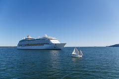 Sailboat and Cruise Ship. Huge, white, luxury cruise ship anchored in blue water with sailboat off starboard bow Royalty Free Stock Images