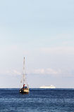 A sailboat and a cruise ship in the ocean Stock Images