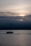 Sailboat in dark sunset #2. Sailboat in dark sunset with hills in the background Stock Photography