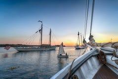 Sailboat Dingy Sails Between Wooden Boats at Sunset. Maine, USA royalty free stock photos