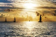 Sailboat and disherman at sunset Stock Photo