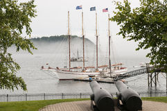 Sailboat at dock in fog. Large, four-masted sailboat at a pier or dock in Bar Harbor, Maine (USA) in fog.  Antique coastal cannon in foreground Royalty Free Stock Photo