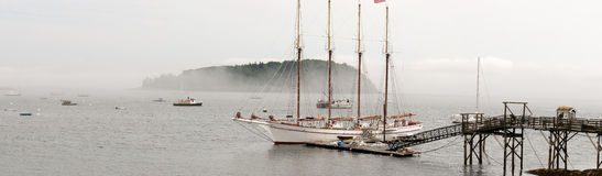 Sailboat at dock in fog. Large, four-masted sailboat at a pier or dock in Bar Harbor, Maine (USA) in fog.  Wide-angle panorama Stock Images