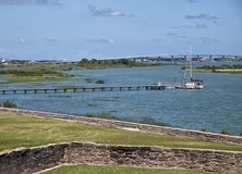Sailboat docked at pier in ocean bay Stock Photography