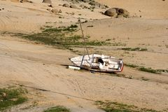 Sailboat on dry lake bed. A sailboat on its side at the bottom of a dry lake or reservoir Stock Images