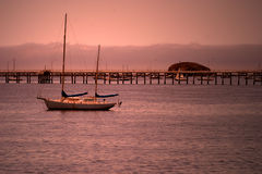 Sailboat at Dusk. A lone sailboat with pier in background Stock Photo
