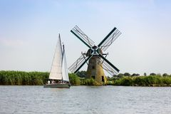 A sailboat and a Dutch windmill on the Kaag royalty free stock photo