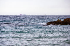 A sailboat and a ferry off the coast of Lloret de Mar. Lloret de Mar has excellent sandy beaches grainy stock photo