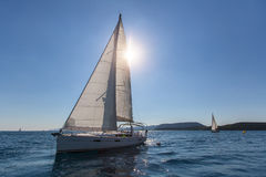 Sailboat at the finish regatta race in the backlight. Travel. Stock Photo