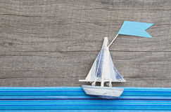 Sailboat with flag on grey wooden background with blue stripes. For a coupon or holiday concept stock photography
