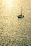 Sailboat floating on the calm sea at sunset. Royalty Free Stock Images