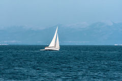 Sailboat floats quickly against the distant mountains Royalty Free Stock Image