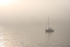 Sailboat on a foggy water. Small single sailboat in fog Stock Photo