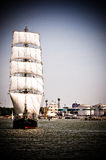 Sailboat on full sails. Sailboat going out of port with full sails up okd film look Royalty Free Stock Images