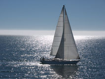 Sailboat gliding on calm sea. Sailboat navigating on calm sea on a beatiful sunny day. Afternoon sun makes the water shine Royalty Free Stock Image