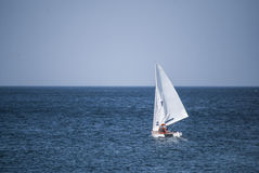 Sailboat gliding over the ocean. Surface Stock Image