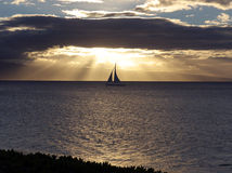 Sailboat gliding at sunset stock photo