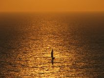 Sailboat on golden ocean Royalty Free Stock Photo