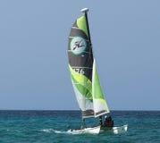 Sailboat With Green And Black Sail Royalty Free Stock Photos