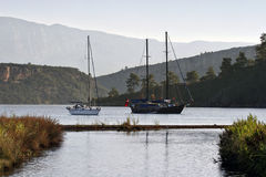 Sailboat and gulet at anchor in a calm bay Royalty Free Stock Photography