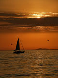 Sailboat and gull at sunset. The ship with open sail in a beautiful sunset, seagulls flying over the Adriatic Sea. Vertical color photo Royalty Free Stock Image