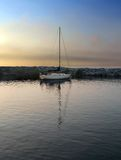 Sailboat in harbor at sundown Stock Photography