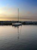 Sailboat in harbor at sundown. Colors play in reflection of sailboat at sunset on Lake Michigan Stock Photography