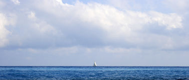 Sailboat on the horizon. Panoramic shot of single sailboat on ocean horizon Stock Images