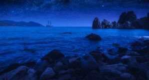 Sailboat on a horizon in mediterranean sea bay at night stock photography