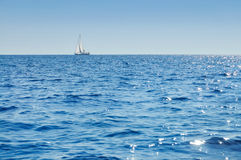 Sailboat at horizon Stock Images