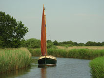 Sailboat Horsey Mere Norfolk Broads. A red sailed boat sailing amongst reeds on the Norfolk Broads on Horsey Mere Royalty Free Stock Photo