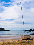 Sailboat on inlet beach. A peaceful view of a small sailboat on the beach of a narrow inlet Stock Photography
