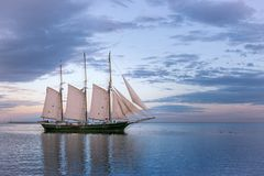 Sailboat on Lake Michigan in Milwaukee, Wisconsin. At sunset with beautiful cloudy skies royalty free stock photography