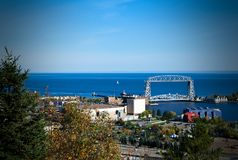 Duluth Aerial Lift Bridge and Lake Superior on a clear afternoon. A sailboat on Lake Superior is seen beyond the iconic Duluth, Minnesota Aerial Lift Bridge Royalty Free Stock Image