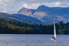 Sailboat in Lake Windermere,  Cumbria, UK. With the forest and mountains in the background shot during a boat trip on the lake Royalty Free Stock Photography